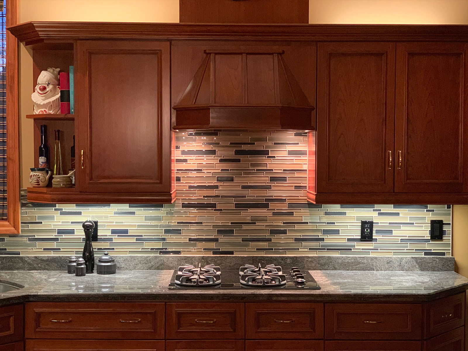 Cherry cabinets with glass back splash and granite countertop